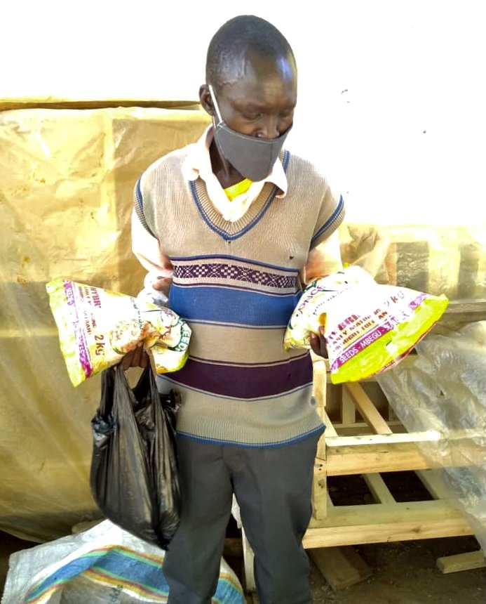 Nsubuga John's Father with Seeds for their Farming Business, Arapai Village Uganda