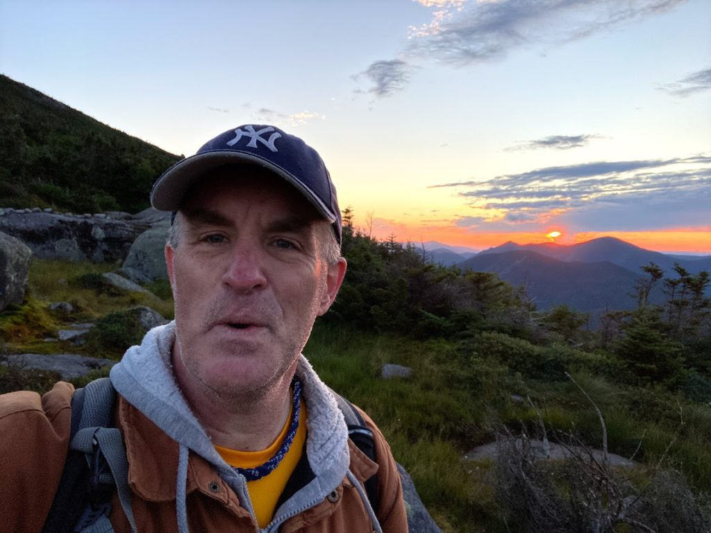 Tim Coming Down Mount Marcy at Sunset with Algonquin Peak Behind